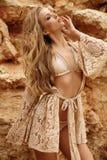 Ursnygg kvinna med blont hår i den eleganta baddräkten som poserar på stranden royaltyfri bild