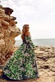 Ursnygg kvinna med blont hår i den eleganta klänningen som poserar på stranden arkivbild