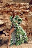 Ursnygg kvinna med blont hår i elegant posera för strandklänning royaltyfria bilder