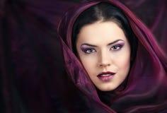 Ursnygg kvinna med den purpura scarfen Arkivbild