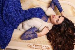 Ursnygg kvinna med långt mörkt hår i den eleganta klänningen som ligger på soffan Arkivbild
