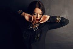Ursnygg kvinna med mörkt hår och ljus makeup med den lyxiga smycket Arkivfoto