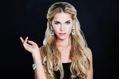 Ursnygg kvinna med makeup, blont lockigt hår och smycken Royaltyfri Bild