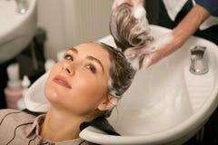 Ursnygg kvinna som har hennes hår att tvättas av frisören royaltyfria foton