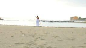 Ursnygg kvinna som inviterar in mot stranden lager videofilmer