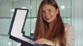 Ursnygg kvinna som ler, medan välja en dyr halsband på smyckenlagret fotografering för bildbyråer