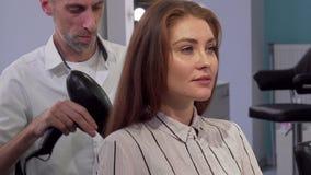 Ursnygg kvinna som ler till kameran, medan att få hennes hårslag torkade lager videofilmer