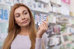 Ursnygg kvinnashopping på apoteket arkivfoton