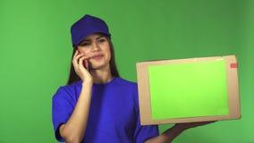 Ursnygg kvinnlig hemsändningarbetare som levererar packen som talar på telefonen stock video