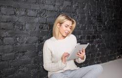 Ursnygg läs- information om kvinnastudent på handlagblocket, sammanträde på ett golv mot tegelstenväggen royaltyfria bilder