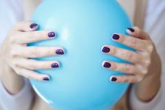 Ursnygg manikyr, mörk lilaanbudfärg spikar polermedel, closeupfoto Kvinnlighänder över enkel bakgrund arkivfoton