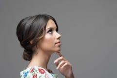 Ursnygg profil av den latinska latinamerikanska skönhetkvinnan med fingret under hakan som tänker och ser upp Royaltyfri Foto