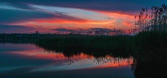 Ursnygg solnedgång med moln reflekterade i sjöns vatten arkivbild