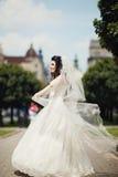 Ursnygg stilfull brud i den vita klänningen för tappning som in går Arkivbilder
