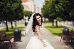 Ursnygg stilfull brunettbrud i den vita klänningen för tappning som in går Royaltyfri Bild