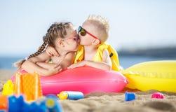 Ursnygg syskongrupp som solbadar på en sandig strand Arkivbilder