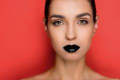 Ursnygg trendig kvinna med svarta kanter som ser kameran Arkivfoton