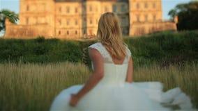Ursnygg ung blond brud som poserar mot till den gamla medeltida slotten i västra Ukraina arkivfilmer