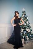 Ursnygg ung kvinna i svart klänning med perfekt makeup och hår royaltyfria foton