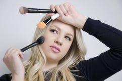 Ursnygg ung kvinna som ser i spegel, medan sätta på makeup Royaltyfria Foton
