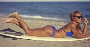 Ursnygg ung kvinna som solbadar i en bikini lager videofilmer