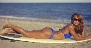 Ursnygg ung kvinna som solbadar i en bikini Arkivfoto