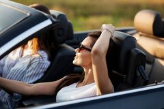 Ursnygg ung mörker-haired ung kvinna i iklädd solglasögon en vit t-skjorta som sitter i en cabriolet och ler på arkivbilder