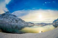 Ursnygg utomhus- sikt av klart vatten i en sjö med en sol som reflekterar, med ett enormt berg som täckas med insnöade Lofoten Arkivbilder