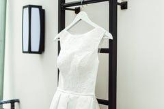 Ursnygg vit bröllopsklänning på en brandstege på balkongen brudtillbehör i en bröllopdag Fotografering för Bildbyråer