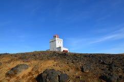 Ursnygga blåa himlar med den Dyrholaey fyren överst av havet Royaltyfri Bild