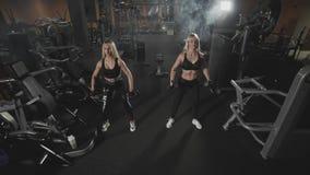 Ursnygga blonda konditionkvinnor som tillsammans övar med hantlar på idrottshallen lager videofilmer