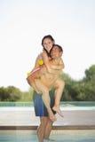 Ursnygga par som har den roliga poolsiden på ferier Royaltyfri Fotografi