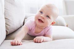 Ursnygga små behandla som ett barn krypning på soffan Royaltyfri Bild