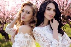 Ursnygga unga kvinnor i den eleganta klänningen som poserar i trädgård med blos Royaltyfria Bilder