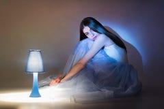 Ursnyggt balettdansörsammanträde bredvid lampan Royaltyfria Bilder