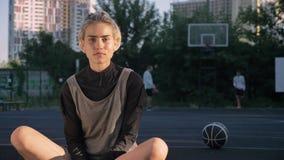 Ursnyggt blont kvinnasammanträde på basketdomstolen och le på kameran, män i bakgrund som spelar, kvinnlig spelare stock video