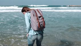 Ursnyggt europeiskt flickaprovvatten på havsstranden Den härliga kvinnan ler på kameran Vind som blåser i hår långsam rörelse arkivfilmer