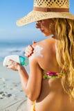 Ursnyggt kvinnasammanträde på stranden i sunhat som applicerar suncream Royaltyfria Foton