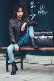 Ursnyggt posera för flicka som utanför sitter på bänken med läderpåsen, hipsterstil royaltyfria bilder