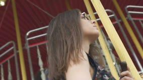 Ursnyggt posera för modell som rider på karusell, nätt kvinna i stadsnöjesfält lager videofilmer