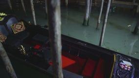 Ursnyggt svart gondolanseende i lerigt och smutsigt vatten av den storslagna kanalen, Venedig lager videofilmer