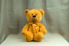 Urso alaranjado de sorriso do brinquedo com uma curva Imagem de Stock Royalty Free