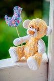 Urso amarelo de assento no banco Fotos de Stock Royalty Free