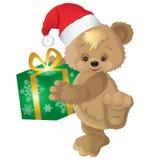 Urso bonito em um chapéu vermelho com o presente do ` s do ano novo em uma caixa Fotografia de Stock