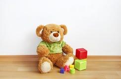 Urso da peluche, cubos no assoalho estratificado Imagem de Stock