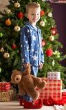 Urso da peluche da terra arrendada do menino na frente da árvore de Natal Imagens de Stock Royalty Free