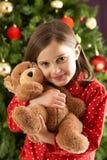 Urso de afago da menina na frente da árvore de Natal fotografia de stock royalty free