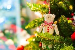 Urso de madeira velho do brinquedo com uma fita vermelha da curva que pendura na árvore de Natal no fundo outras decorações e fes Fotografia de Stock Royalty Free