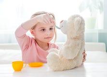 Urso de peluche de alimentação do brinquedo da menina bonito Imagens de Stock Royalty Free