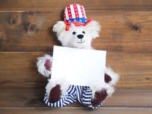 Urso de peluche americano de sorriso que guarda o cartão branco para 4o julho h Imagem de Stock